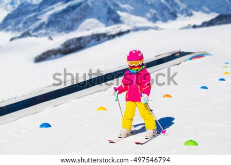 Child in alpine ski school with magic carpet lift and colorful training cones going downhill in the mountains on a sunny winter day. Little skier kid learning and exercising skiing on a slope. #497546794