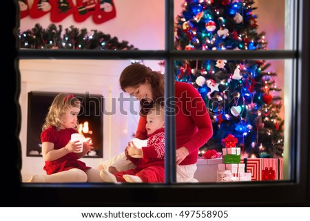 Family on Christmas eve at fireplace. Mother and little kids opening Xmas presents. Children with gift boxes. Living room with traditional fire place and decorated tree. Cozy winter evening at home. #497558905