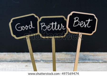 Business message Good, Better, Best written with chalk on wooden mini blackboard labels, defocused chalkboard and wood table in background #497569474