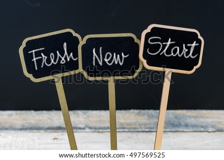 Business message Fresh New Start written with chalk on wooden mini blackboard labels, defocused chalkboard and wood table in background #497569525