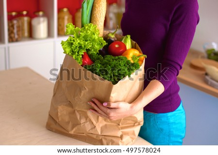Healthy positive happy woman holding a paper shopping bag full of fruit and vegetables #497578024