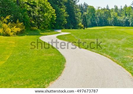 Curved sidewalk, path, trail at the empty street. Neighborhood scenery. #497673787