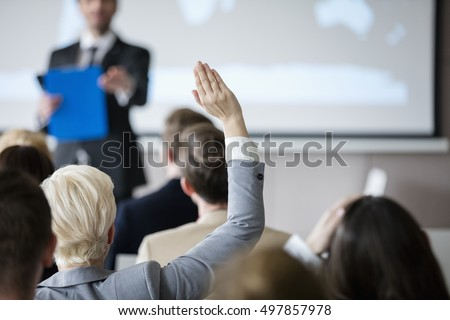 Rear view of businesswoman raising hand during seminar Royalty-Free Stock Photo #497857978