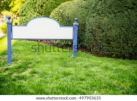 framed entrance sign with empty space for text. welcome blank sign in grass. the concept of houses and property for sale. mock up.