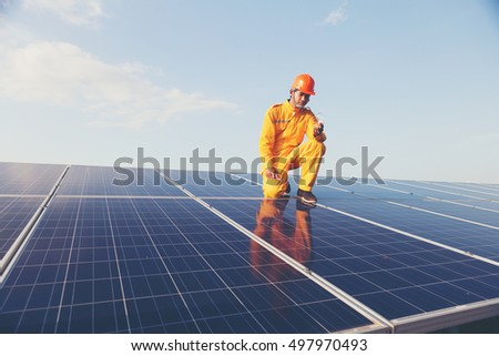 Engineers checking solar panels,Holding the bulb on the Solar Panel. Solar Energy ,The concepts of Clean Energy. #497970493