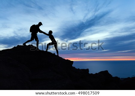 Teamwork couple hiking, help each other, trust assistance and silhouette in mountains, sunset over ocean. Team of climbers man and woman helping hand on mountain top, inspirational climbing team. #498017509