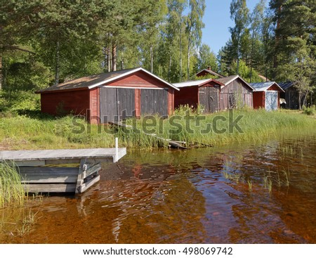 Group of red boathouse by the waterside, pine trees and blue sky in the background #498069742
