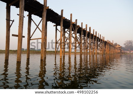 Old wooden bridge in early morning, sunrise, U Bein Bridge is a crossing that spans the Taungthaman Lake near Amarapura, Myanmar #498102256