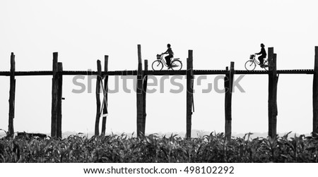 Black and white photo of old wooden bridge and silhouettes of two girls riding bikes , U Bein Bridge is a crossing that spans the Taungthaman Lake near Amarapura, Myanmar #498102292