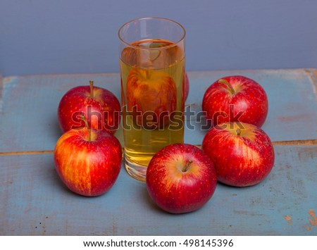 Glass of apple juice and a red apples on a blue old wooden background #498145396