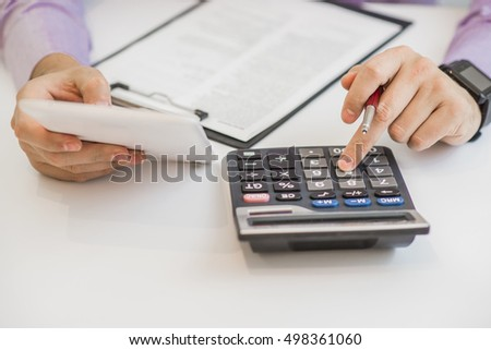 Close up of male accountant or banker making calculations. Savings, finances and economy concept #498361060