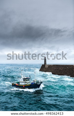 Fishing vessel under storm arriving at pier.  It's a boat or ship used to catch fish in the sea. Fishing can be affected by storms. Storms implies conditions like strong wind, precipitations or rain. #498362413