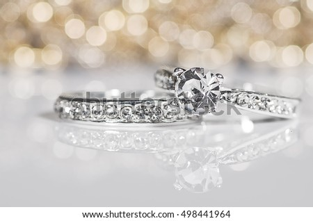 Silver Rings with diamonds on the white surface with golden reflections in the background. #498441964