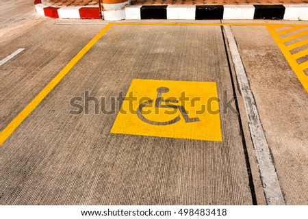 Handicapped people parking lot with the wheel chair icon on concrete surface. #498483418