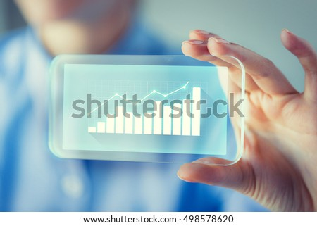 business, technology, satistics and people concept - close up of woman hand holding and showing transparent smartphone screen with diagram chart #498578620