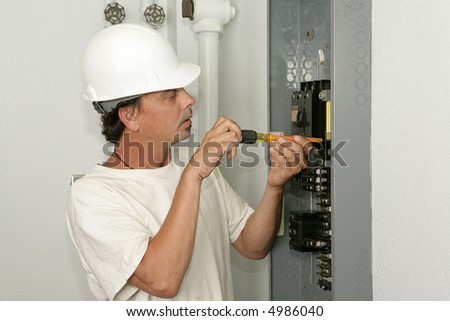 An electrician installing a breaker in an electric panel.  Model is an actual electrician and all work is being performed according to industry codes and safety practices. #4986040