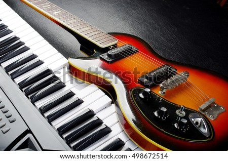 Music keyboard and electric guitar. Royalty-Free Stock Photo #498672514