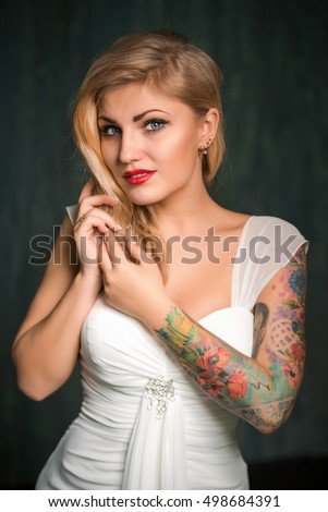 young beautiful blond woman in the white dress. blonde woman with  a tattoo of flowers on her shoulder and hand, red lipstick, dark background, like Marilyn Monroe, Bride with tattoos