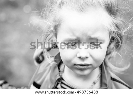 Portrait of a sad girl with closed eyes in black and white