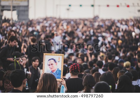 Bangkok, Thailand- October 14, 2016: thai people hold the portrait of King Bhumibol Adulyadej after a convoy carrying the body of the King from Siriraj Hospital to the Royal Palace. proud to be thai #498797260
