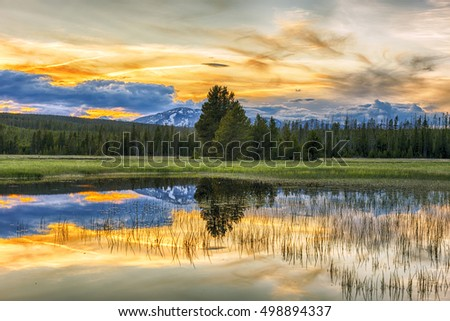 Beautiful vivid sunset at Yellowstone National Park. Mountains and sky is reflecting in a lake. Wyoming, USA #498894337