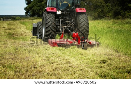 Farming: Large red tractor moving green farmers pasture, motion close up  #498920602