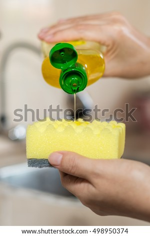 Pouring yellow lemon dishwasher liquid onto a kitchen sponge Royalty-Free Stock Photo #498950374