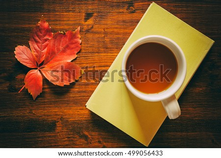 Cup of tea on a book and autumnal leaf seen from above in vintage style #499056433