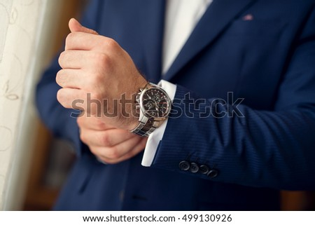 Cropped shot of a man wearing elegant blue suit and a wrist watch. #499130926