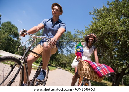 a young man and a beautiful African American girl enjoying a bike ride in nature on a sunny summer day #499158463