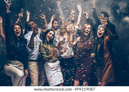 Party fun. Group of beautiful young people throwing colorful confetti and looking happy #499219087