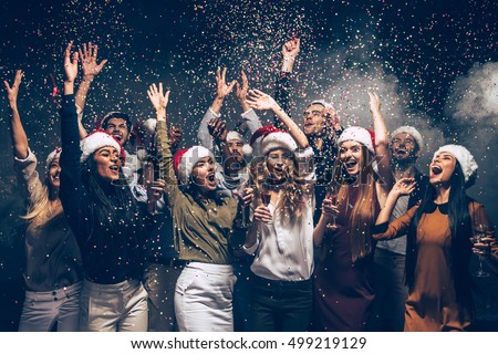 Celebrating New Year together. Group of beautiful young people in Santa hats throwing colorful confetti and looking happy Royalty-Free Stock Photo #499219129