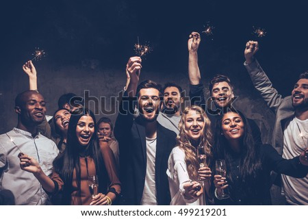 Party with friends. Group of cheerful young people carrying sparklers and champagne flutes Royalty-Free Stock Photo #499219201