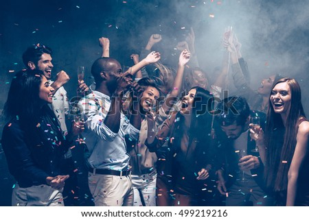 Carefree fun. Group of beautiful young people throwing colorful confetti and looking happy #499219216