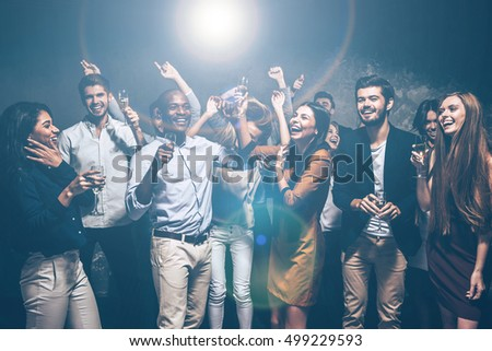 Best party ever. Group of beautiful young people dancing together and looking happy #499229593