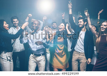 Party with friends. Group of beautiful young people dancing together and looking happy #499229599