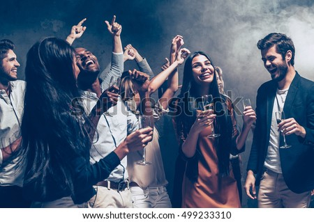 Enjoying cool party. Group of beautiful young people dancing with champagne flutes and looking happy #499233310