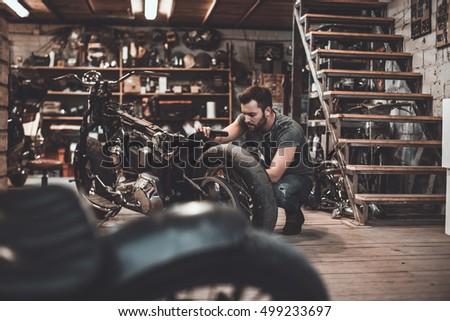 Man repairing bike. Confident young man repairing motorcycle in repair shop