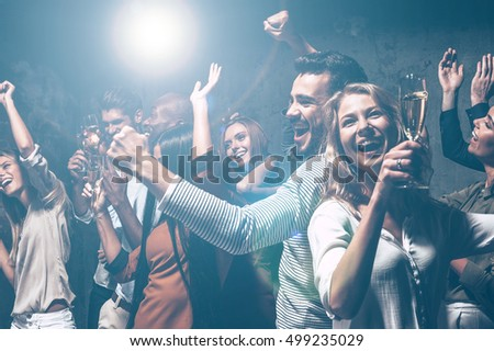 Dancing all night long. Group of beautiful young people dancing with champagne flutes and looking happy #499235029