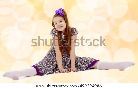 Caucasian little girl with a big purple bow on her head. Girl shows how to do the splits.On a brown blurred background with white snowflakes. #499394986
