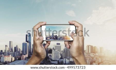 Hand using smartphone taking photo of Bangkok city in sunrise