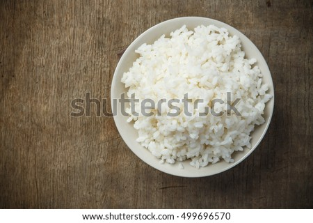 Bowl of organic rice on wooden table #499696570