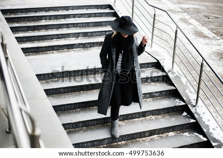 Woman in a hat walking down the street by stairs, cold, autumn, city. With no face. Wearing grey jacket and blond hair.