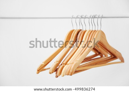 Wooden coat hangers on clothes rail and white background #499836274
