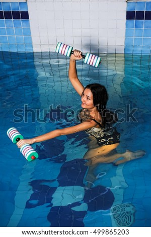 Young attractive woman doing aqua gym exercise with water dumbbell in swimming pool #499865203