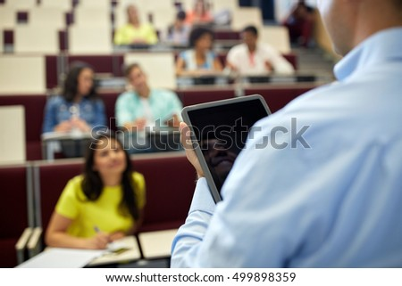 education, high school, university, learning and people concept - close up of teacher with tablet pc computer and students at lecture hall #499898359