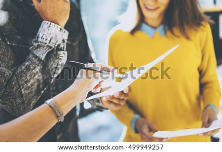 Closeup of man holding the papers in his hands and woman signing document. Coworkers team working in sunny office near the window.Horizontal, blurred background