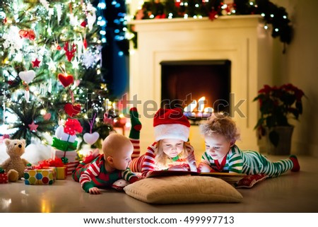 Happy little kids in matching red and green striped pajamas decorate Christmas tree in beautiful living room with traditional fire place. Children opening presents on Xmas eve. #499997713