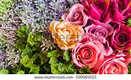Decorative background artificial  roses and flowers on a wall. #500085025