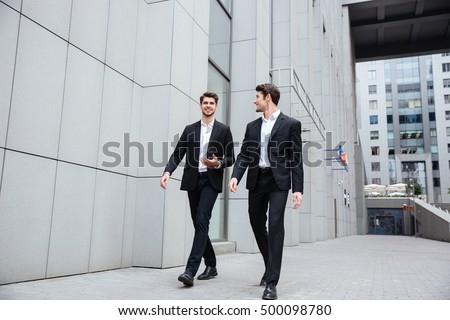 Two smiling young businessmen walking and talking in the city #500098780